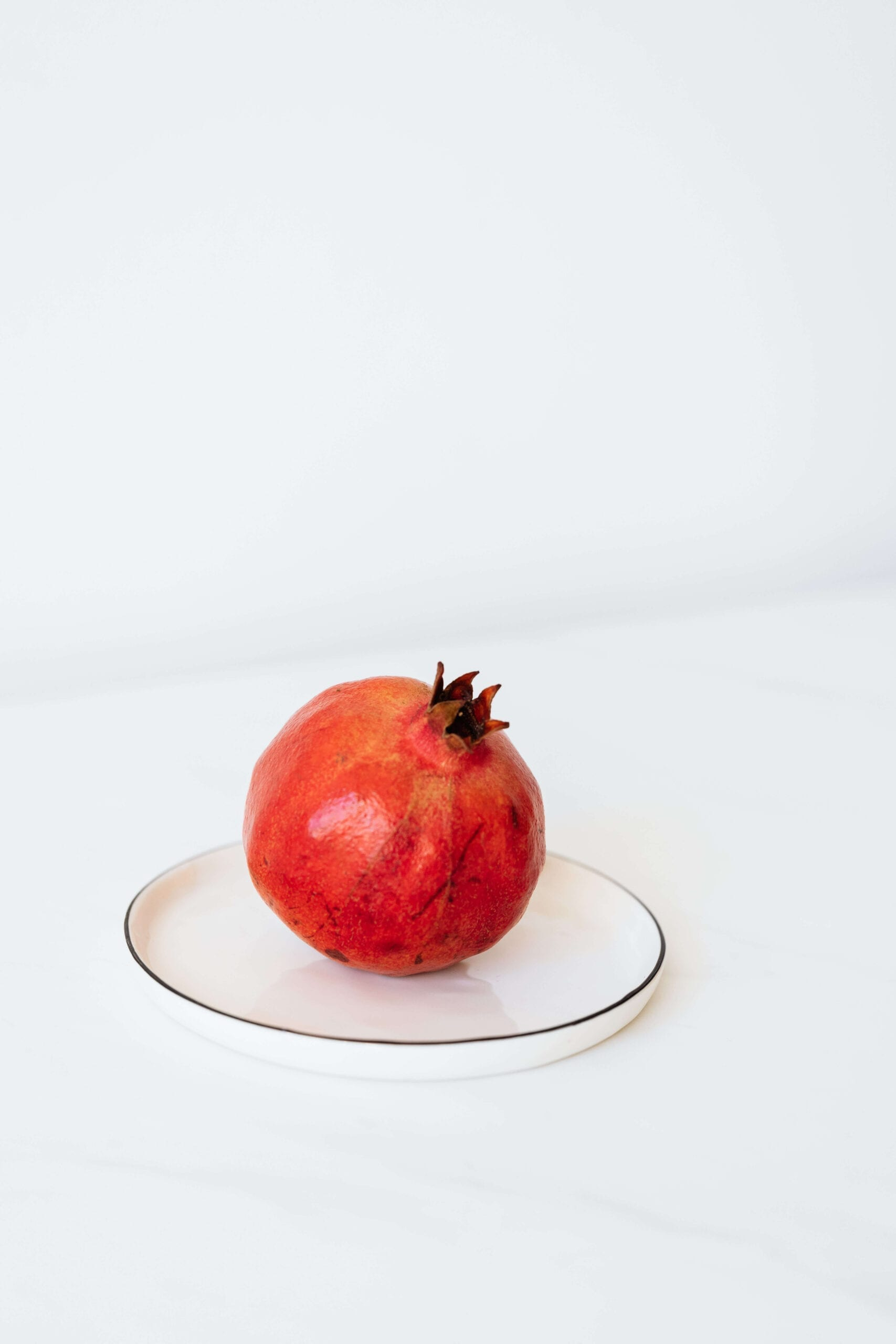 ripe-pomegranate-on-metal-plate-on-white-table-4230630